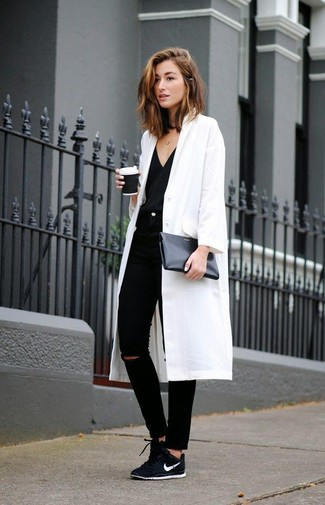Consider pairing a white coat with black ripped slim jeans for a standout ensemble. Mix things up by wearing black low top sneakers.