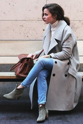 Rock a grey coat with blue skinny jeans for a comfortable outfit that's also put together nicely. This outfit is complemented perfectly with grey suede ankle boots.