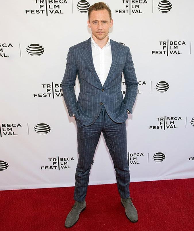 d58e81a10b4cc Tenue de Tom Hiddleston  Costume à rayures verticales bleu, Chemise à  manches longues blanche, Chaussures derby en daim grises   Mode hommes