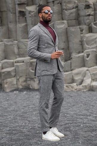 Opte pour un costume en laine gris avec un pull à col roulé bordeaux pour un look pointu et élégant. Décoince cette tenue avec une paire de des baskets basses en cuir blanches.