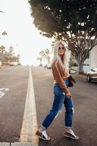 500+ Fall Outfits For Women: For an off-duty look, wear a brown crew-neck sweater and blue ripped boyfriend jeans — these items play pretty good together. Complete this outfit with a pair of brown suede low top sneakers to instantly switch up the look. This one is a smart pick when it comes to a cool look that transitions easily into fall.