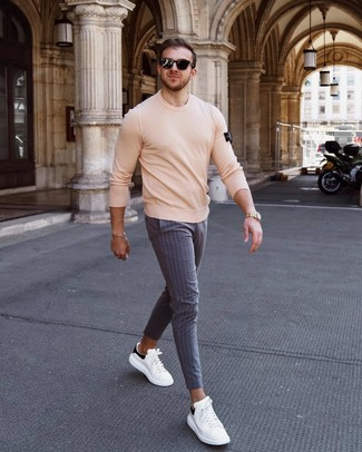 How to wear: beige crew-neck sweater, grey vertical striped chinos, white and black leather low top sneakers, black sunglasses