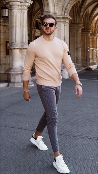 Beige Crew-neck Sweater with White and Black Leather Low Top Sneakers Casual Outfits For Men: For a laid-back and cool ensemble, choose a beige crew-neck sweater and grey vertical striped chinos — these two items fit perfectly well together. If you're clueless about how to round off, a pair of white and black leather low top sneakers is a never-failing option.