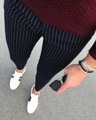 How to wear: burgundy crew-neck sweater, black vertical striped dress pants, white leather low top sneakers, black sunglasses