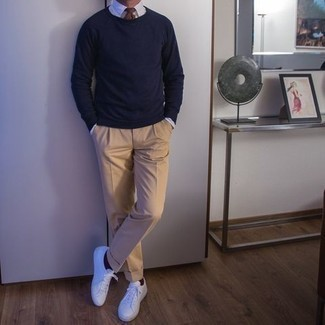 White Canvas Low Top Sneakers Outfits For Men: This elegant combo of a navy crew-neck sweater and khaki dress pants is a must-try look for any modern man. If you need to immediately dial down your look with a pair of shoes, complement your look with white canvas low top sneakers.