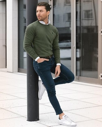 How to wear: olive crew-neck sweater, white dress shirt, navy skinny jeans, white leather low top sneakers