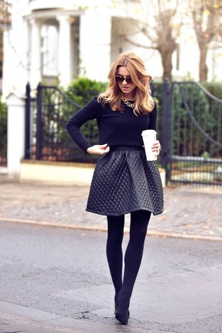 A black crew-neck sweater and a black full skirt is a great combination to carry you throughout the day. Elevate this ensemble with black suede pumps.