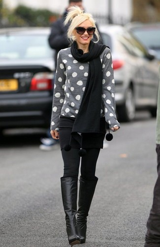 How to Wear Black Leather Knee High Boots Casually: This casual combination of a grey polka dot crew-neck sweater and black leggings is clean, incredibly stylish and oh-so-easy to replicate! And if you want to effortlesslly glam up this getup with a pair of shoes, complete your ensemble with a pair of black leather knee high boots.
