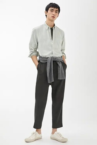 Charcoal Chinos Outfits: A grey crew-neck sweater and charcoal chinos are a great combo to take you throughout the day and into the night. In the shoe department, go for something on the casual end of the spectrum and finish off your outfit with white canvas low top sneakers.