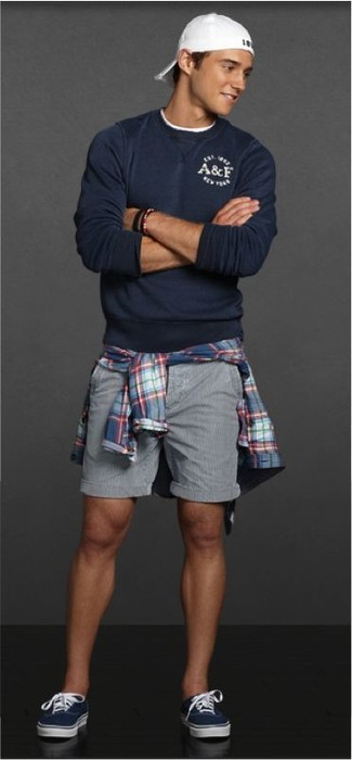 How to wear: navy crew-neck sweater, blue plaid long sleeve shirt, grey shorts, navy low top sneakers
