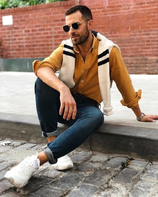 How to wear: beige horizontal striped crew-neck sweater, mustard long sleeve shirt, navy skinny jeans, white athletic shoes