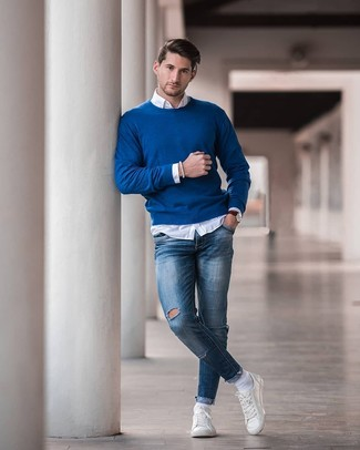 How to wear: blue crew-neck sweater, white long sleeve shirt, blue ripped skinny jeans, white leather low top sneakers