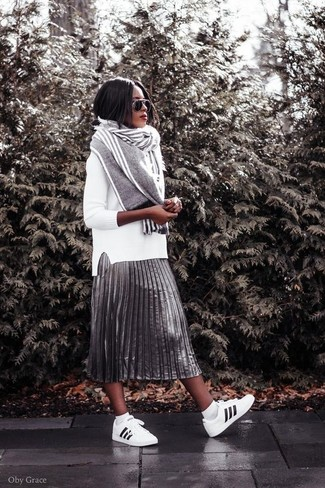 Master the effortlessly chic look in a white crew-neck sweater and a silver pleated midi skirt. Grab a pair of white and black leather low top sneakers to make the ensemble current. This one will play especially well come warmer days.