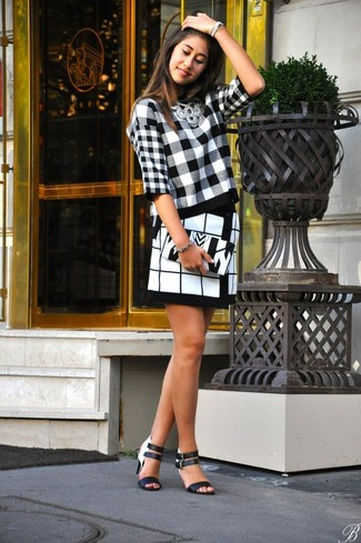 A monochrome plaid crew-neck sweater and a white and black check mini skirt is a smart combination worth integrating into your wardrobe. Elevate this ensemble with monochrome leather heeled sandals.