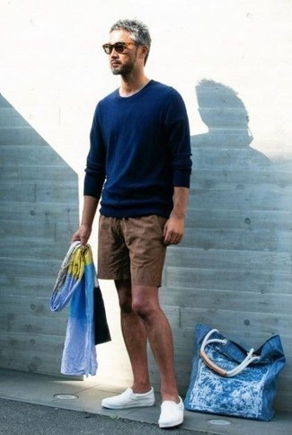 How to Wear a Navy Crew-neck Sweater For Men: A navy crew-neck sweater and brown shorts are absolute menswear staples if you're picking out an off-duty wardrobe that holds to the highest sartorial standards. The whole look comes together when you introduce white canvas slip-on sneakers to this ensemble.