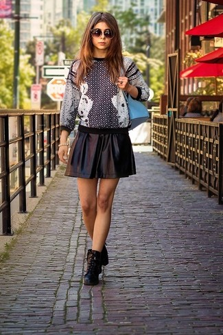 How to wear: black and white print crew-neck sweater, black leather skater skirt, black leather lace-up ankle boots, light blue backpack