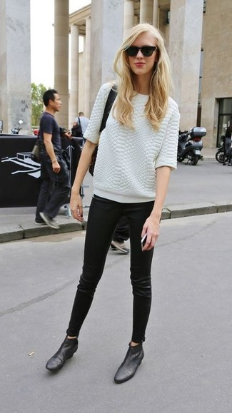 A white textured crew-neck pullover and black leather slim jeans are perfect for both running errands and a night out. Black leather booties will add elegance to an otherwise simple look.