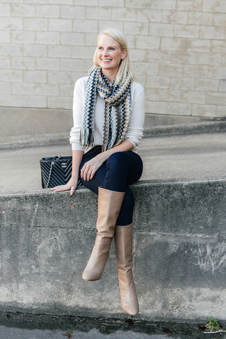 How to wear: white crew-neck sweater, navy skinny jeans, tan leather knee high boots, black quilted leather satchel bag