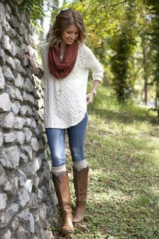 This combination of a white textured crew-neck sweater and blue ripped skinny jeans is perfect for off-duty occasions. Elevate your getup with brown leather knee high boots.