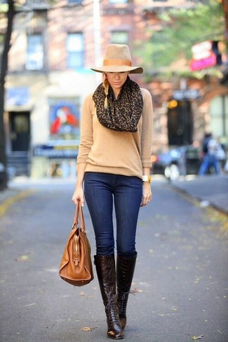 If you're a fan of classic pairings, then you'll like this pairing of a tan crew-neck sweater and deep blue slim jeans. Perk up your look with dark brown leather knee high boots. When you're having one of those dreary autumn days, sometimes only a knockout look like this one can get you to face the outside world.