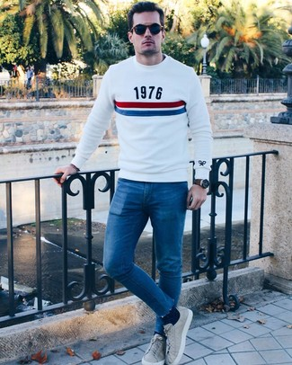 How to wear: white print crew-neck sweater, blue skinny jeans, grey leather low top sneakers, navy sunglasses