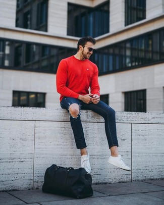 How to wear: red crew-neck sweater, navy ripped skinny jeans, white leather low top sneakers, black leather holdall