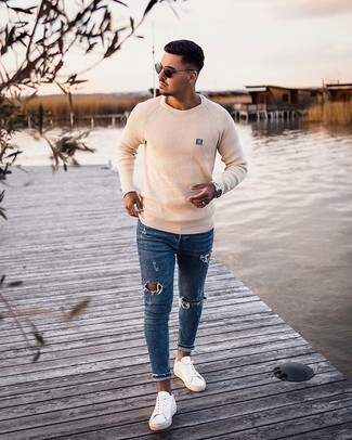 Beige Crew-neck Sweater Relaxed Outfits For Men: This combination of a beige crew-neck sweater and blue ripped skinny jeans is on the casual side but is also seriously stylish and really dapper. Tap into some David Beckham dapperness and lift up your outfit with a pair of white canvas low top sneakers.