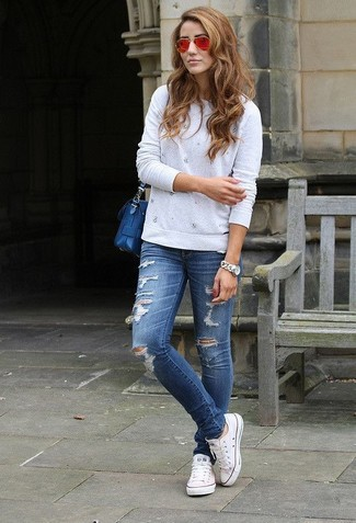 How to wear: grey embellished crew-neck sweater, navy ripped skinny jeans, white low top sneakers, blue leather crossbody bag