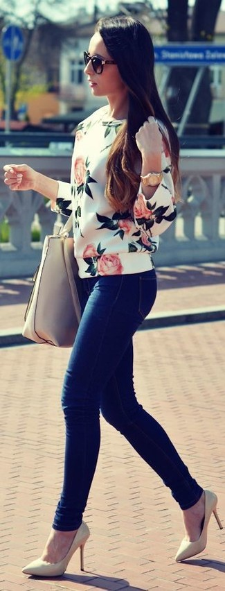 For an on-trend look without the need to sacrifice on comfort, we love this combination of a white floral crew-neck sweater and navy blue slim jeans. Bring instant glamour to your getup with beige leather pumps. This ensemble is super comfortable and will help you out in awkward transition weather.
