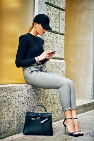 Master the effortlessly chic look in a black crew-neck sweater and grey slim pants. Make black leather heeled sandals your footwear choice to instantly up the chic factor of any outfit.