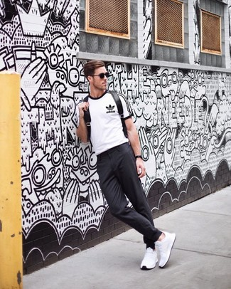 How to wear: white and black print crew-neck t-shirt, charcoal chinos, white athletic shoes, black leather backpack
