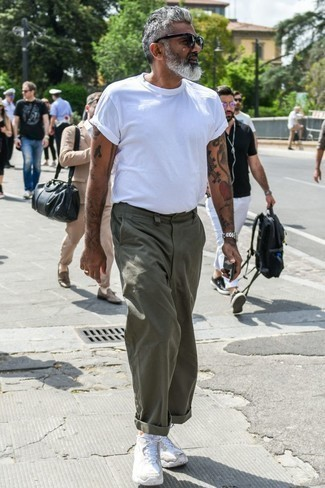How to Wear Olive Chinos In Summer: Such must-haves as a white crew-neck t-shirt and olive chinos are an easy way to inject effortless cool into your day-to-day casual collection. To inject a more laid-back feel into this getup, introduce white athletic shoes to the mix. This outfit is also ideal if you're looking for hot weather wear to make a boring day more tolerable.