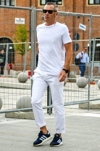 How to Wear White Chinos: A white crew-neck t-shirt and white chinos are absolute menswear essentials if you're planning an off-duty closet that holds to the highest sartorial standards. Complement your ensemble with navy and white athletic shoes to keep the getup fresh.