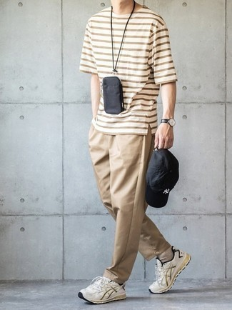 Khaki Chinos Outfits: Try teaming a brown horizontal striped crew-neck t-shirt with khaki chinos for neat menswear style. Why not add white athletic shoes to this outfit for a more relaxed spin?