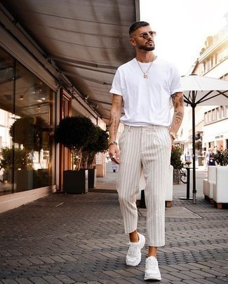 Men's Outfits 2021: Fashionable and comfortable, this casual combination of a white crew-neck t-shirt and beige vertical striped chinos will provide you with a multitude of styling possibilities. Throw white athletic shoes into the mix to effortlessly dial up the wow factor of your look.