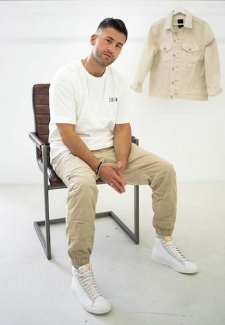 How to Wear White Canvas High Top Sneakers For Men: For an ensemble that's extremely easy but can be worn in a multitude of different ways, make a white crew-neck t-shirt and khaki chinos your outfit choice. For a more relaxed twist, complement this ensemble with a pair of white canvas high top sneakers.