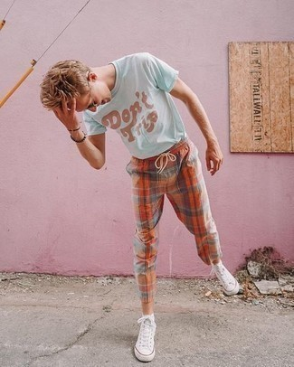 White Canvas High Top Sneakers Hot Weather Outfits For Men: Busy off-duty days require a straightforward yet casually dapper ensemble, such as a light blue print crew-neck t-shirt and orange check chinos. White canvas high top sneakers will pull the whole thing together.