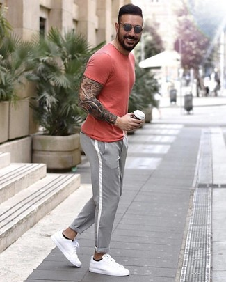 How to wear: red crew-neck t-shirt, grey chinos, white leather low top sneakers, grey sunglasses