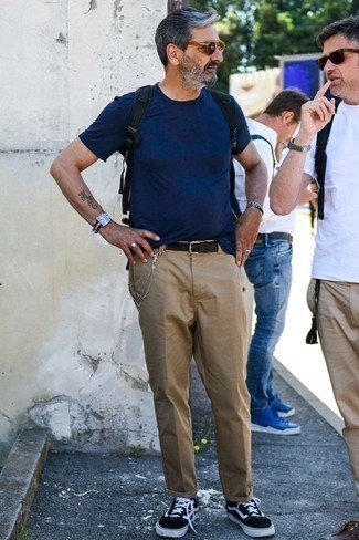How to Wear Chinos: A navy crew-neck t-shirt and chinos married together are a great match. If you're hesitant about how to finish off, a pair of black and white low top sneakers is a good idea.