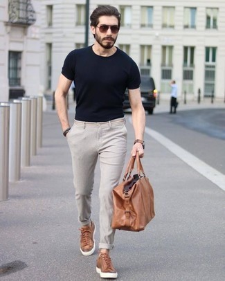 How to Wear Beige Chinos: Fashionable and practical, this casual combination of a black crew-neck t-shirt and beige chinos delivers amazing styling opportunities. Tobacco leather low top sneakers pull the outfit together.