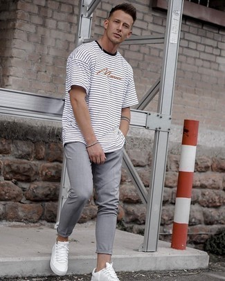 White and Red Leather Low Top Sneakers Outfits For Men: This relaxed pairing of a white and black horizontal striped crew-neck t-shirt and grey chinos is a surefire option when you need to look sharp in a flash. Let your outfit coordination prowess really shine by finishing off this getup with a pair of white and red leather low top sneakers.