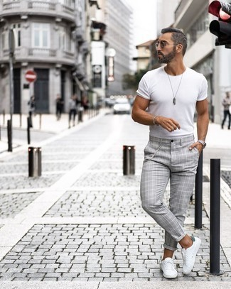 White and Green Leather Low Top Sneakers Outfits For Men: This combo of a white crew-neck t-shirt and grey plaid chinos delivers comfort and laid-back cool. Look at how nice this look pairs with a pair of white and green leather low top sneakers.