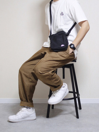 Brown Corduroy Chinos Outfits: Pair a white crew-neck t-shirt with brown corduroy chinos for a functional outfit that's also put together nicely. White leather low top sneakers integrate seamlessly within a myriad of getups.