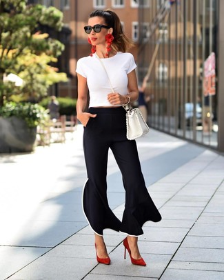 How to Wear Red Suede Pumps: This relaxed pairing of a white crew-neck t-shirt and black flare pants is super easy to put together without a second thought, helping you look chic and ready for anything without spending a ton of time combing through your closet. A pair of red suede pumps effortlesslly ramps up the wow factor of any ensemble.