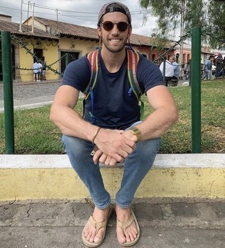 How to Wear Brown Sunglasses In a Relaxed Way For Men: A navy crew-neck t-shirt and brown sunglasses are a good combination to take you throughout the day and into the night. Take a more casual approach with footwear and choose a pair of beige leather flip flops.