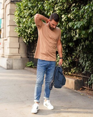 How to wear: tan crew-neck t-shirt, blue jeans, white leather low top sneakers, navy canvas backpack