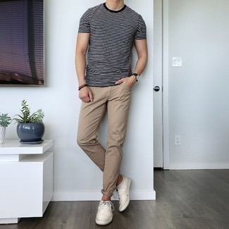 Men's Outfits 2021: The combination of a black and white horizontal striped crew-neck t-shirt and khaki jeans makes for a solid casual ensemble. When not sure as to what to wear when it comes to shoes, go with beige canvas low top sneakers.