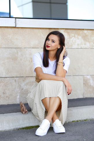Rock a white crew-neck tee with a gold pleated midi skirt for a Sunday lunch with friends. White low top sneakers will give your look an on-trend feel.