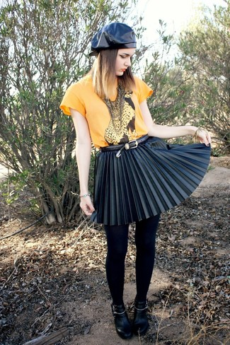 If you love staying-in clothes which are stylish enough to wear out, consider this combination of a green-yellow t-shirt and a black pleated leather mini skirt. Got bored with this outfit? Enter black leather ankle boots to shake things up. On not so cold afternoons, rock this summer-to-fall look and look absolutely amazing.