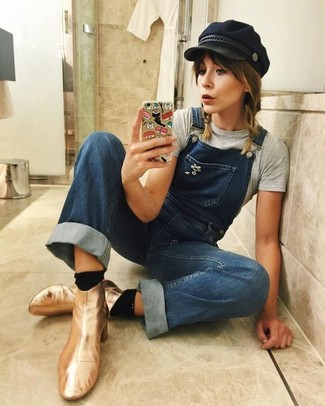 How to wear: grey crew-neck t-shirt, blue denim overalls, gold leather ankle boots, black flat cap